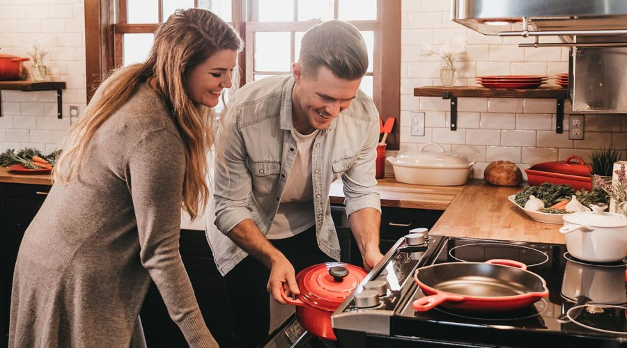 young couple using kitchen appliances
