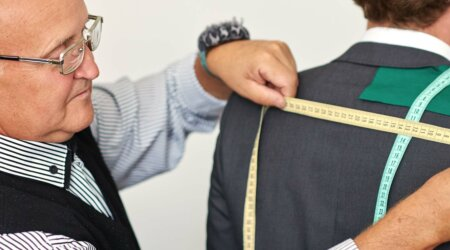 man tailoring a suit to demonstrate quality