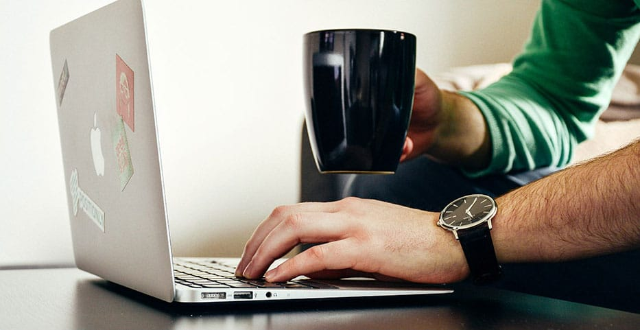 man working on laptop with coffee